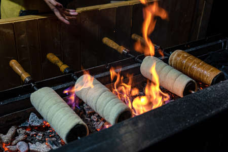 A chimney cake is baked over an open charcoal grill hungary