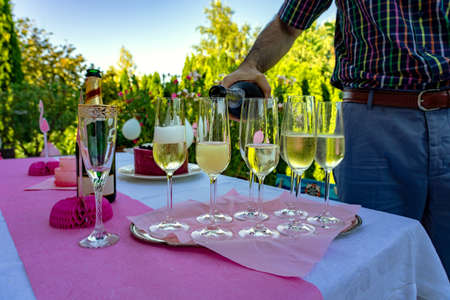 Pour champagne on a pink outdoor party