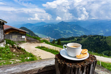 drinking a cup of caffee with breakfast over the mountains in tyrol on a hut terrasse