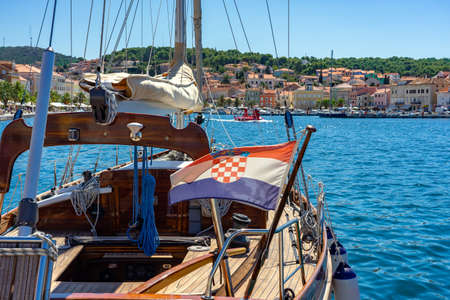 Schönes Segelboot aus Holz in Mali Losinj Island Port Kroatien mit bunten Gebäuden