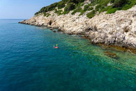 senior man snorkeling next to the rocky seashore on Croatia islands with turquoise water . Banco de Imagens