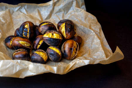 close up roasted chestnuts on paper and black stone background .