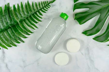 bio cosmetic product on marble background with leaves