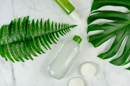 bio cosmetic products on marble background with leaves