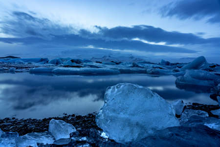 iceland glacier jokulsarlon in the evening icebergs floating on the cold peaceful water after sunset with dramatic sky