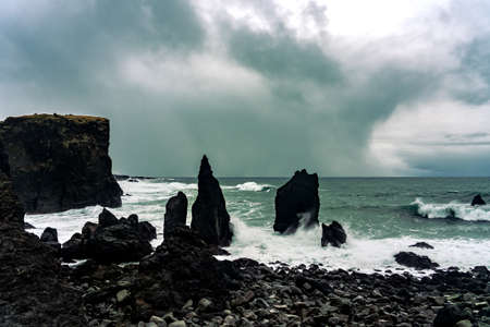 the coast of reykjanes peninsula in Iceland Reykjanesviti with a big rock in the water and stormy sky