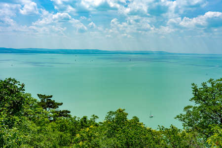 Man hiking on a hill next to the Lake Balaton showing sunbeams over the sail boats in summer Standard-Bild