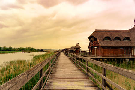 peaceful nature at the Lake Fertő in Hungary with wooden pier bungalows cabins on the lake and straw in the water at sunset Stockfoto
