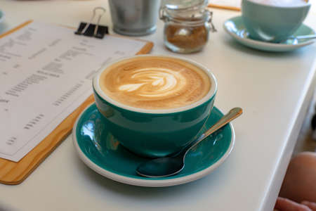 caffee latte macchiato cappuccino in blue turquoise mug in cafe house with milk foam art .