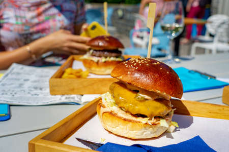 Eating burger on social event with friends together in a restautant outdoor on a board . Foto de archivo