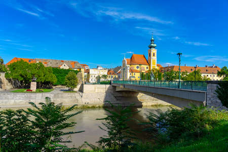Gyor city with the Raba river and a carmelite church in Hungary .