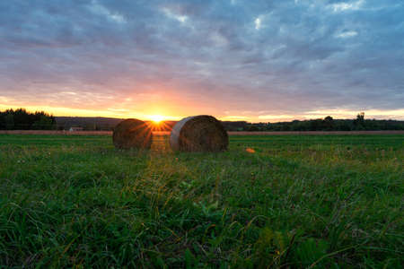 Beautiful sunset on the field in Őrség Hungary with sunbeams and bales