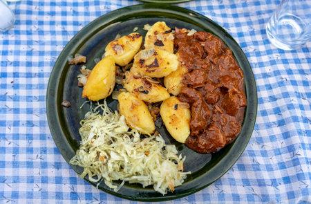 traditional hungarian Őrség style Dödölle pastry potato dumpling with pörkölt stew and cabbage