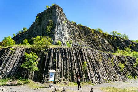 Hegyestu geological basalt cliff in kali basin hungary near Koveskal with a tourist woman 免版税图像