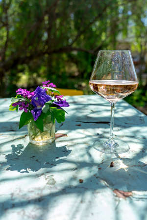 Vintage Outdoor table in a garden with a glass of rose wine spritze and flowers