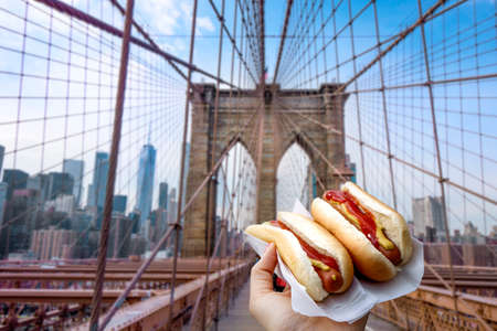 Holding two hot dogs in NYC on the Brooklyn Bridge