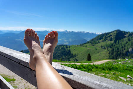 woman relaxing on a terrasse of a tirol alm hutte with feet up and mountain view