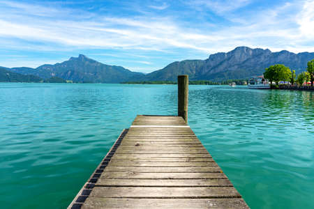 Mondsee with mountains vier from a wooden rustic dock pier 免版税图像