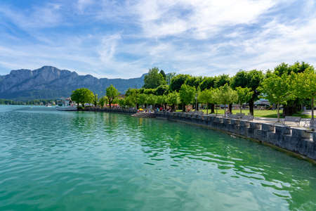 06.05.2021 - Mondsee, Austria: Mondsee with mountains and the beautiful promenade with people and ships