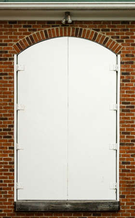 White wooden doors with brick arch and wood sill