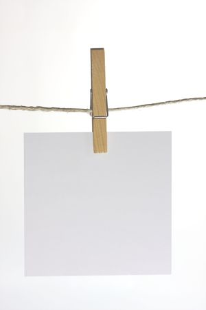 sheet of paper  hanging on a peg from a line photo