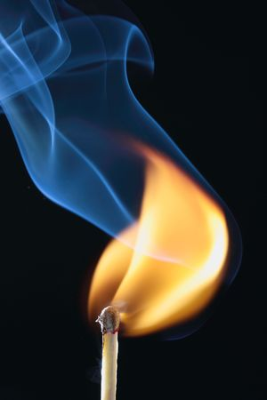 ignited match with blue smoke on black background
