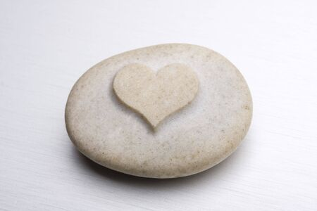 metal surface: a stone with an engraved heart on a metal surface Stock Photo