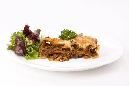 piece of lasagna al forno with some salad