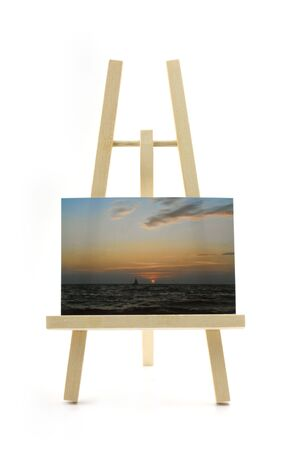 wooden easel with sunset photo on white background Stock Photo