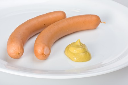 a pair of wieners on a white plate photo