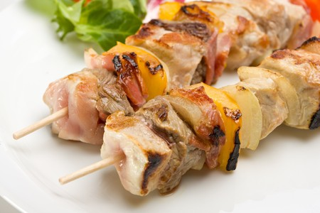 shashlik on a plate with a tomato and salad leaf Stock Photo
