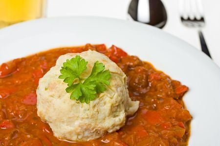 hungarian goulash and a bread dumpling on a white plate photo