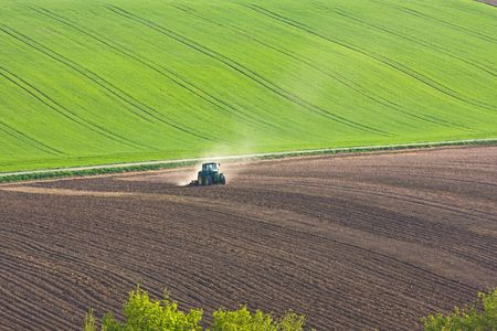 tractor throwing up dust on farmland Stock Photo
