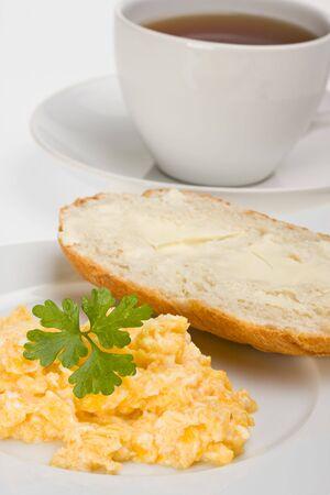scrambled eggs and bun on a plate