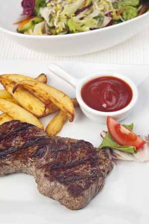 steak and french fries on a plate photo
