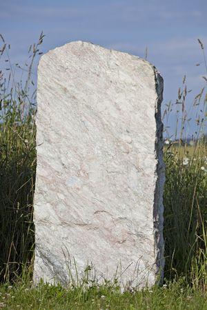 single empty granite gravestone on a grass meadow Stock Photo