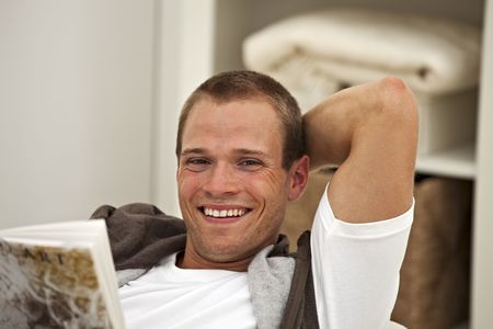 smiling young man reading a book Stock Photo