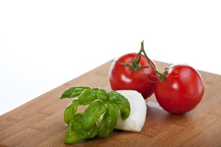tomatoes, mozzarella and basil while making insalada caprese photo