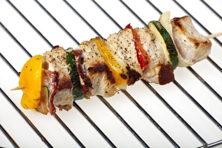brazier: grilled shashlik on a charcoal grate over a white background