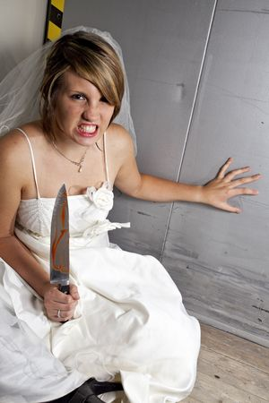angry young bride with a bloody knife in an elevator photo