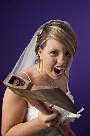 angry young bride with an axe on a dark blue background photo