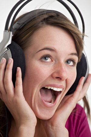 young woman screams for joy while listening to music photo