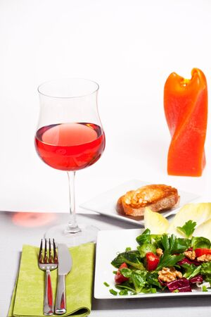 mixed salad on a white plate with a glass of rose photo