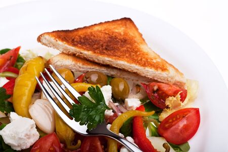 greek salad on a plate with a slice of toast bread photo