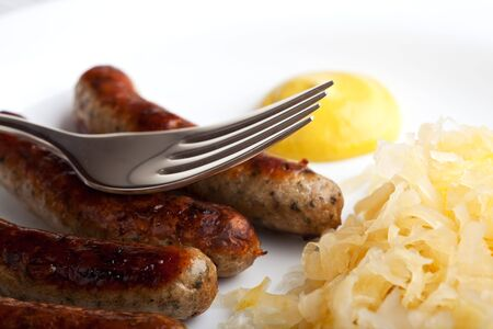fried sausages,mustard and sauerkraut on a plate with a fork Stock Photo - 6139826