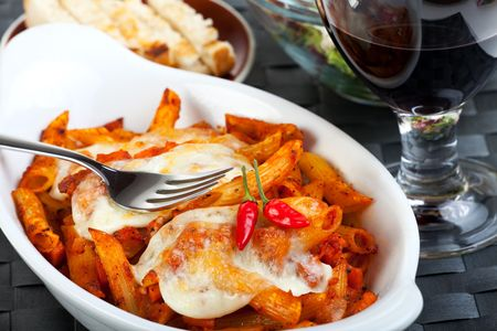 rigatoni pasta with tomato sauce and melted cheese photo