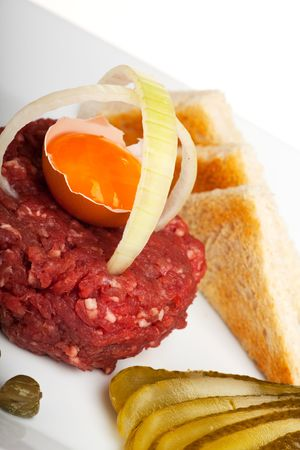 steak tartar with an onion ring and an open egg photo