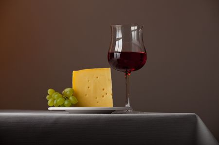 piece of cheese,a bunch of grapes and red wine photo