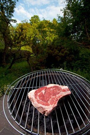 t bone steak: t bone steak on a grill outdoors