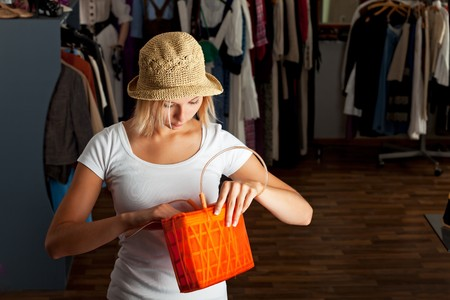 young woman searching her handbag in a boutique photo